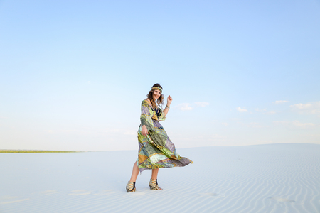 Woman wearing green beach robe and swimsuit standing in sand background. Concept of fashion, summer clothes collection and desert photo session.