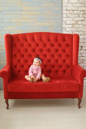 Photo pour Little girl wearing pink sweater sitting on red sofa. Concept of babies and interior. - image libre de droit