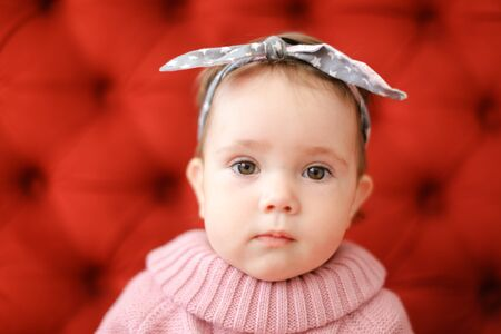 Photo pour Closeup female baby wearing pink sweater sitting in red background. Concept of babies and photo session. - image libre de droit