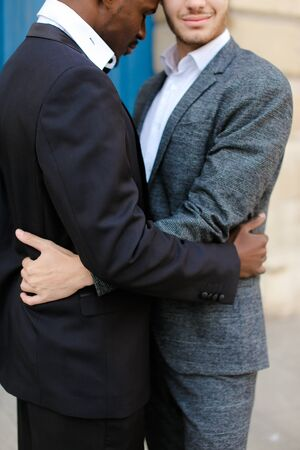 Photo for Afro american happy man hugging caucasian guy in door background, wearing suit. Concept of same sex couple and gays. - Royalty Free Image