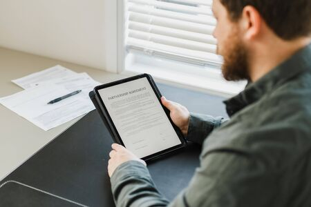 Photo pour Close up man reading partnership agreement ready to be filled on tablet. Concept of filling documents and business project. - image libre de droit