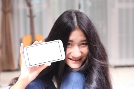 Asian beautiful girl smiling happy using a smartphone . Mixed race Asian Caucasian pretty model