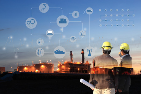 Foto de two engineer on site , Industry 4.0 concept image.Oil refinery at twilight with cyber and physical system icons diagram on industrial factory and infrastructure background. - Imagen libre de derechos