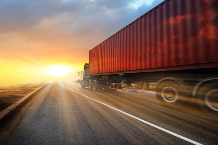 Foto de Generic big trucks speeding on the highway at sunset - Transport industry concept , big truck containers - Imagen libre de derechos