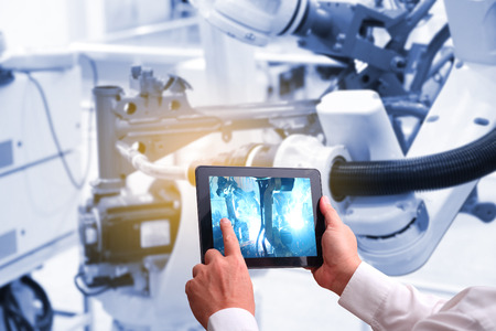 Photo pour industry 4.0 ,  concept  of Man hand holding tablet with Augmented reality screen software and blue tone of automate wireless Robot arm in smart factory background. mixed media  - image libre de droit