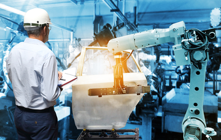 Photo pour Man hand holding QC check with automate wireless Robot arm in smart factory background. Mixed media of welding robot in the automotive parts industry - image libre de droit