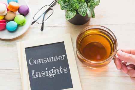 Concept Consumer Insights message on wood boards. Macaroons and glass Tea on table. Vintage tone.