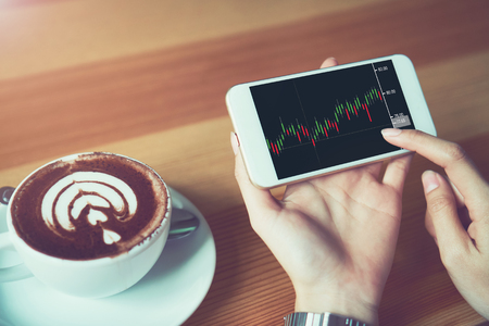 The woman holds the phone on a table with a graphical screen to invest the stock's value. Investment concepts that rely on decision-making information, vintage effect.