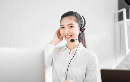 Photo pour Beautiful Asian woman consultant wearing microphone headset of customer support phone operator at workplace. - image libre de droit