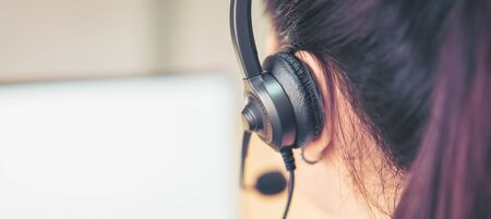 Photo pour Back view of woman consultant wearing microphone headset of customer support phone operator at workplace. proportion of the banner for ads. - image libre de droit
