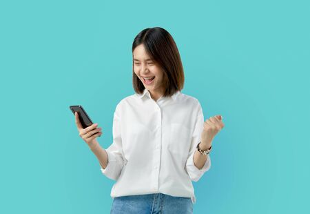 Photo pour Young smiling Asian woman holding smart phone with fist hand and excited for success on light blue background. - image libre de droit