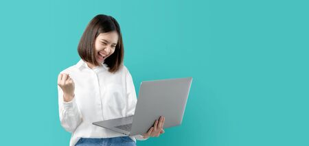 Photo pour Young Asian woman smiling holding laptop computer with fist hand and excited for success on light blue background. - image libre de droit
