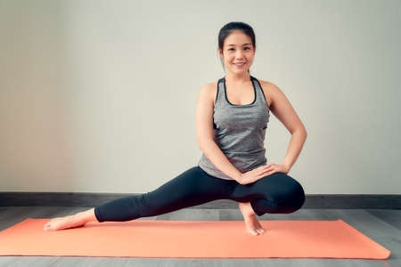 Smiling Asian woman wearing sportswear practicing yoga on orange mat in house. wellness concept.