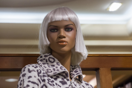 Mannequin brown or black with white wig in clothes shop window