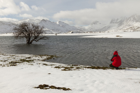 Man squatting on the edge of the water. Marsh Lake in the mountains in winter snow - Hombre en cuclillas en el borde del agua.  Lago de pantano en las montañas  con nieve en invierno