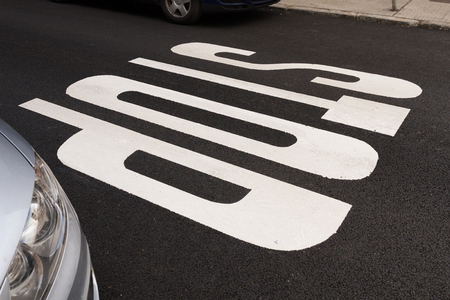 Stop road markings, painted in white on the asphalt Between two cars, parked