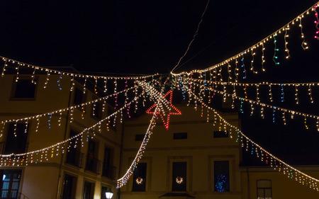 Christmas lights in night city with star of Bethlehem in the middle - Iluminación navideña en nocturno de ciudad con estrella de Belen en el centro // luces, navidad, estrella, ciudad, colores, noche, farolas, ventanas, edificios, central, rojo, puntos,
