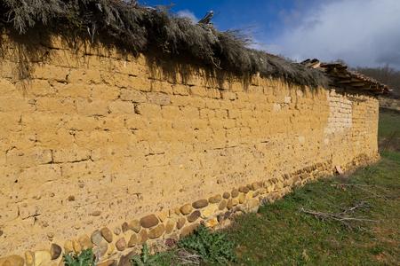 Old rural construction. Adobe wall covered with dried heather branches - Construccion rural antigua. Muro de adobe con cubierta de ramas de brezo secas /// muro, adobe, rural, pared, construccion, antigua, vieja, brezos, ramas, seco, soleado, dia, nadie,