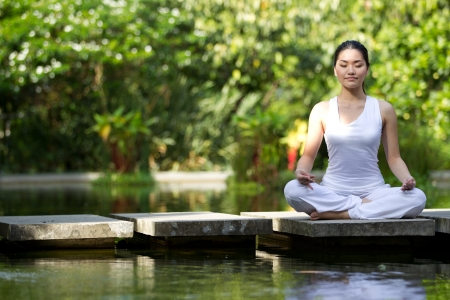 Foto de Woman in white Performing yoga in natural setting - Imagen libre de derechos