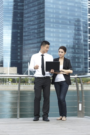 Asian Business man and woman using a Laptop outsideの写真素材