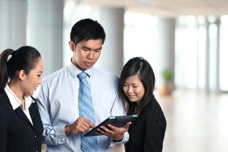Three Asian business people looking at the screen of Digital Tablet