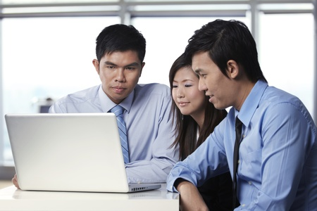Asian business colleagues working around a laptopの写真素材
