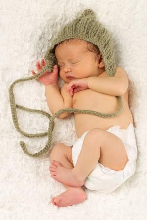 Foto de Newborn Baby boy sleeping while wearing a hat on his head. - Imagen libre de derechos