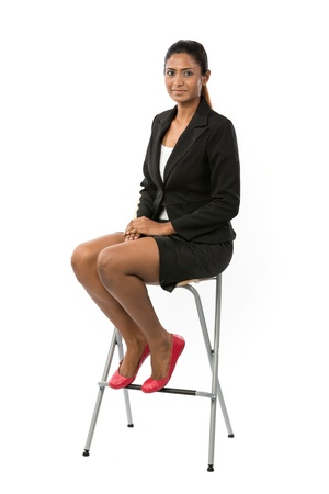 Full length portrait of an Asian Business woman sitting on a chair. Isolated on white background.
