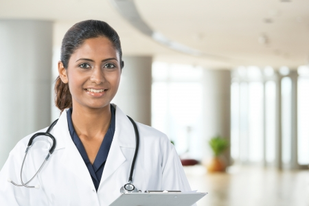 Indian doctor wearing a white coat with stethoscope. The photo has been composed so there is plenty of space for text on the right.