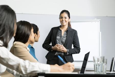 Photo pour Indian woman standing up doing a presentation at a business meeting. - image libre de droit