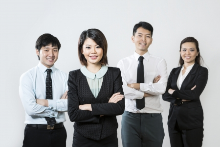 Chinese business woman with her team out of focus behind her.の写真素材
