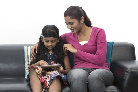 Photo for Indian Mother And Daughter Using digital touchpad At Home on sofa - Royalty Free Image