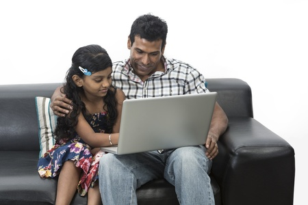 Indian father and daughter at home using a laptop together on the sofa.