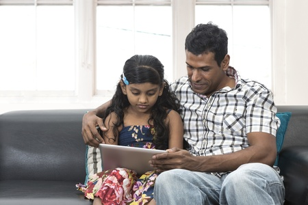 Indian father and daughter at home using digital touchpad tablet together on sofa.