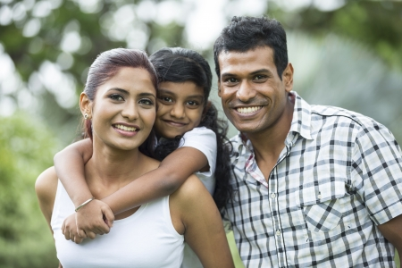 Happy Indian family. Father, mother and daughter in the park