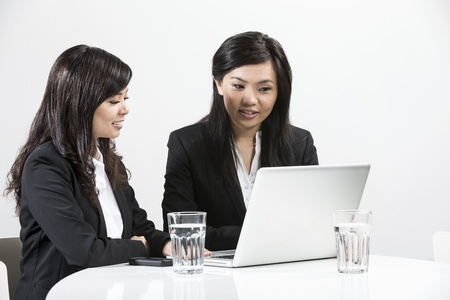 Two Chinese business women people having a meeting togetherの写真素材