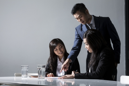 Three Chinese Business people meeting in office to discuss a project