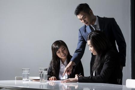 Foto de Three Chinese Business people meeting in office to discuss a project - Imagen libre de derechos