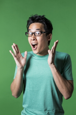 Surprised and amazed looking Asian man standing against green background.