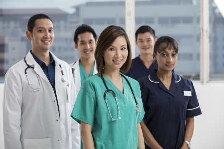Group of doctors and nurses standing in a hospital. Multi-ethnic team of caucasian, Chinese and indian medical staff.