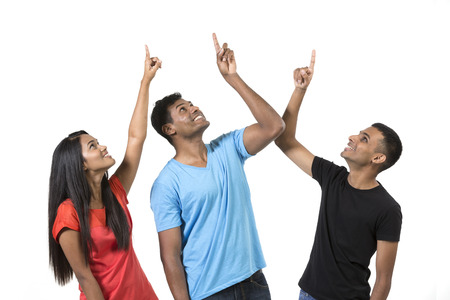 Group of happy Indian friends pointing upwards. Isolated on a white background.