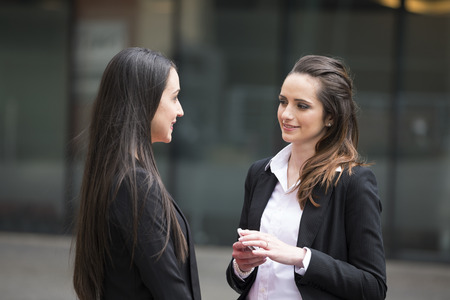 Photo pour Two business women standing outside talking to each other. - image libre de droit