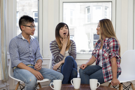 Group of three Asian friends at home talking to each other. Woman in the middle is yawning. Concept about being bored and tired.