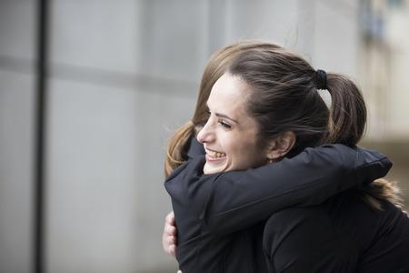 Photo pour Two happy Businesswomen hugging each other outside office building. - image libre de droit