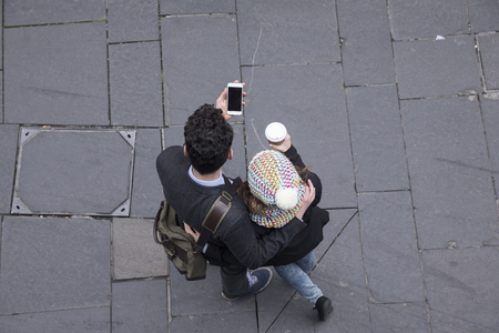 High angle view of a couple walking down the street using a Smart Phone. Young man and woman walking together.