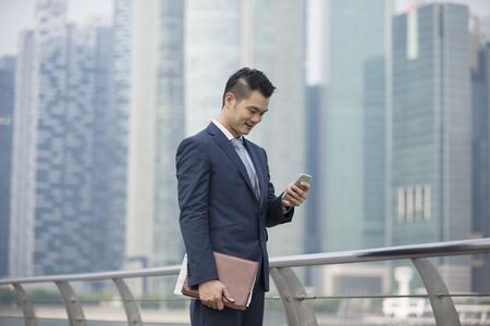 Foto de Chinese businessman standing outdoors and using his Smart phone in modern Asian city. - Imagen libre de derechos