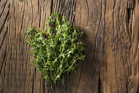 Bunch of fresh thyme sitting on a rustic wooden board.