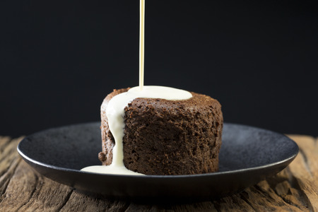 Fresh cream being poured over a Chocolate Lava Cake. Chocolate pudding sitting on a rustic wooden table.