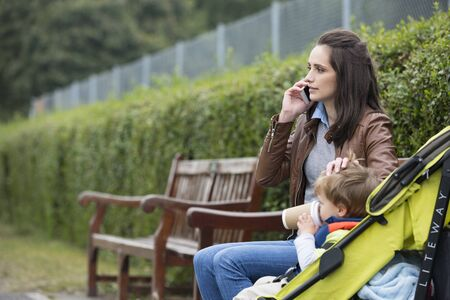 Foto per Busy Mother using mobile phone with toddler sitting in pram. - Immagine Royalty Free