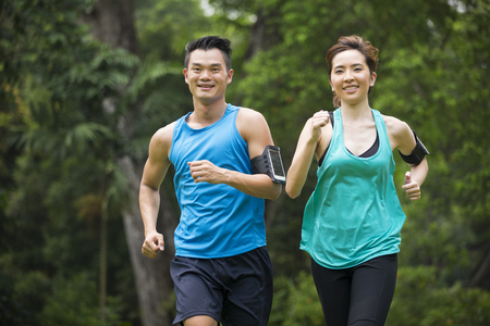 Photo for Athletic Asian man and woman running outdoors. Action and healthy lifestyle concept. - Royalty Free Image